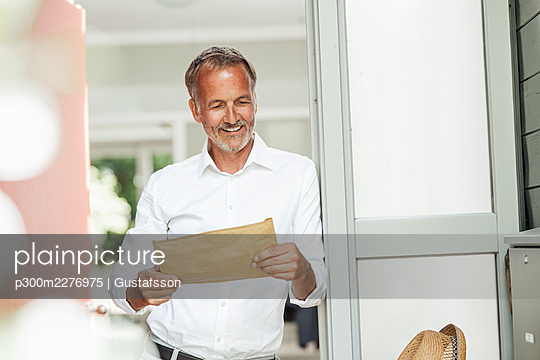 Smiling mature man looking at parcel held at front door - p300m2276975 by Gustafsson