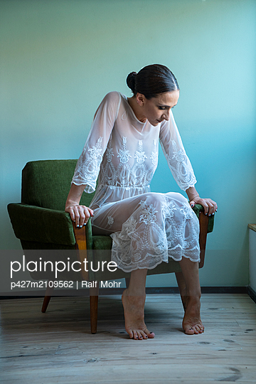Woman sitting in armchair - p427m2109562 by Ralf Mohr