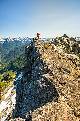 Trail runner stands on mountain summit, edge of a cliff. - p1166m2212400 by Cavan Images