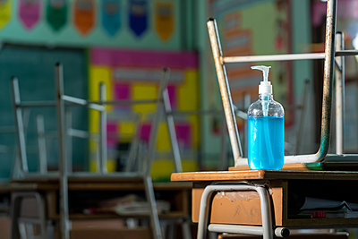 Disinfectant at elementary school student classroom desk. - p1166m2212763 by Cavan Images