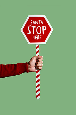 Man holding a sign that reads santa stop here on a green background - p1423m2222541 by JUAN MOYANO