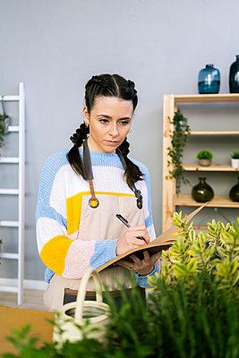 Young woman working in a gardening laboratory or plant shop - p300m2274589 von Giorgio Fochesato