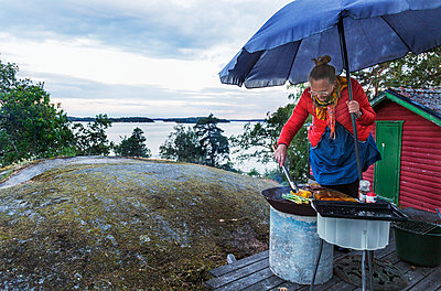 Woman having barbecue - p312m2101624 by Pernille Tofte