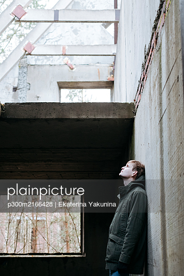 Man leaning at concrete wall of a ruin looking up - p300m2166428 by Ekaterina Yakunina