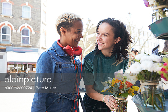 Smiling lesbian couple looking at each other while buying bouquet at market - p300m2290724 by Pete Muller