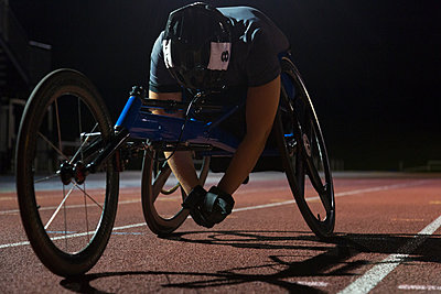 Tired paraplegic athlete resting on sports track after wheelchair race at night - p1023m2067604 by Martin Barraud