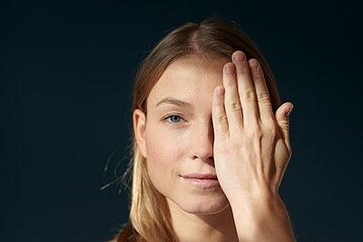 Frau verdeckt ein Auge mit der Hand - p1124m1589413 von Willing-Holtz