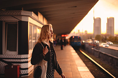 Thoughtful young woman waiting for train at subway station at sunset - p1166m2153555 by Cavan Images
