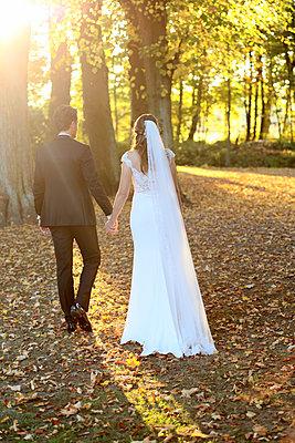 Brautpaar Hand in Hand im Park - p1258m2082692 von Peter Hamel