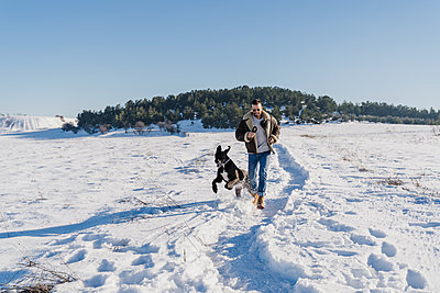 Playful man with dog running in snow on sunny day - p300m2250978 by Eva Blanco