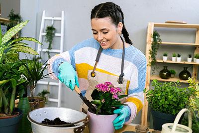 Young woman working in a gardening laboratory or plant shop - p300m2274599 von Giorgio Fochesato