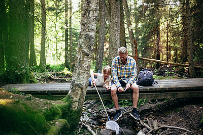 Father with backpack talking to daughter while sitting on footbridge in forest - p426m2213165 by Maskot