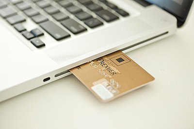 Credit card sticking out of side of laptop computer - p623m894315f by Gabriel Sanchez