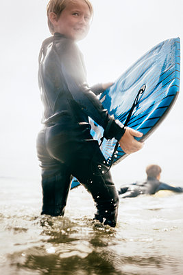 Portrait of young boy wearing wet suit, carrying surfboard into ocean, Santa Barbara, California, USA. - p924m2208569 by JFCreatives