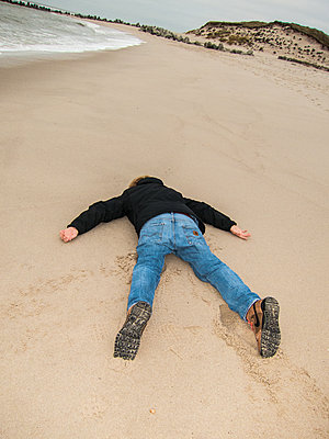 Person lying face down on sandy beach - p930m1200531 by Ignatio Bravo