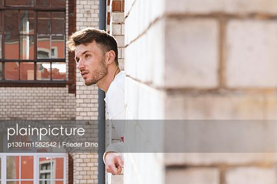 Mann lehnt sich aus einem Fenster  - p1301m1582542 von Delia Baum