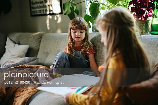 Sisters reading book on sofa - p312m2190430 by Matilda Holmqvist