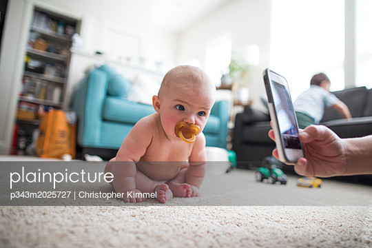 Parent photographing sitting baby - p343m2025727 by Christopher Kimmel