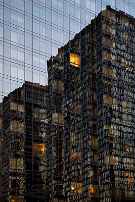 Tower blocks reflecting in glass front of high rise - p1057m1466865 by Stephen Shepherd