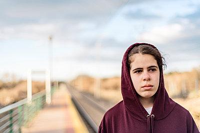 Thoughtful teenage girl wearing hooded shirt at railroad station platform - p1166m1571079 by Cavan Social