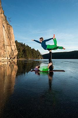 Couple doing yoga on frozen lake - p312m1472101 by Fredrik Schlyter
