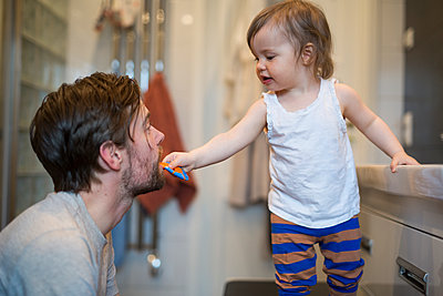 Girl brushing dads teeth - p312m2161750 by Victoria Henriksson