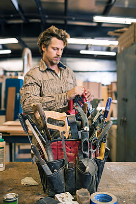 Carpenter standing by tool belt on table in workshop - p426m1062576f by Maskot