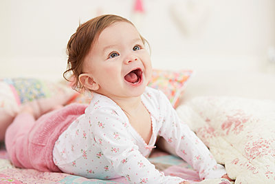 Portrait of baby girl, lying on her front, laughing - p429m1418455 by Emma Kim