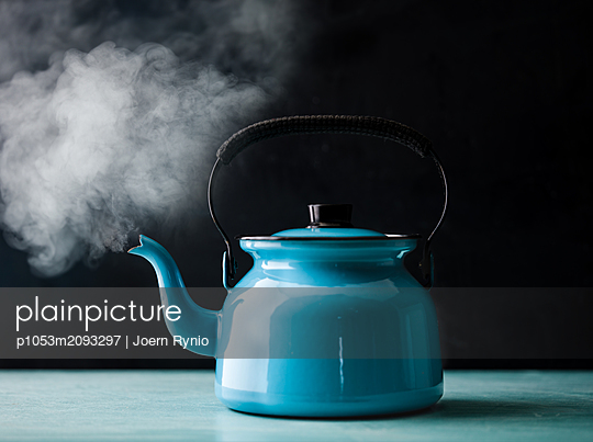 Steaming kettle with boiling water against black background - p1053m2093297 by Joern Rynio