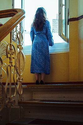 Frau steht am Treppenhaus-Fenster - p045m2014782 von Jasmin Sander