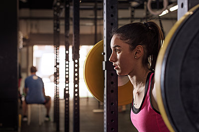 Determined female athlete lifting barbell in health club - p1166m1154099 by Cavan Images