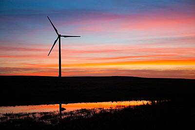 Silhouette windmill on field against cloudy sky during sunset - p1166m1473845 by Cavan Images