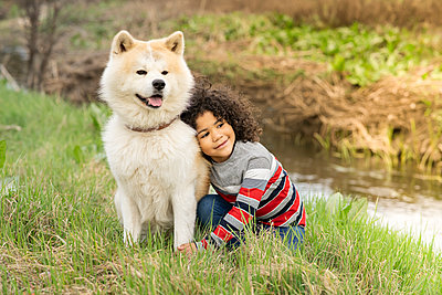 Smiling boy looking away while leaning on dog in nature - p300m2265883 by Jose Carlos Ichiro