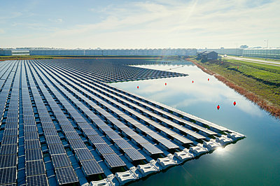 Floating solar panels installed on water supply of neighbouring greenhouses, elevated view, Netherlands - p429m2058282 by Mischa Keijser