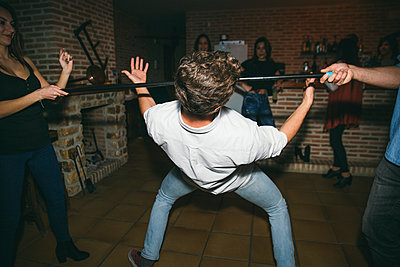 Friends dancing limbo in nightclub - p555m1412841 by Inuk Studio