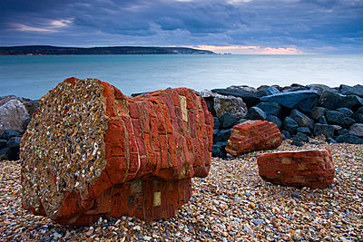 Coastal defences along Hurst Spit. In the distance the Isle of Wight and the Needles - p8714106 by Adam Burton
