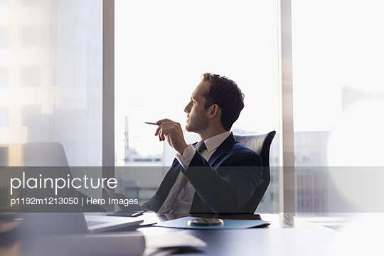 Pensive male lawyer at laptop looking away in conference room