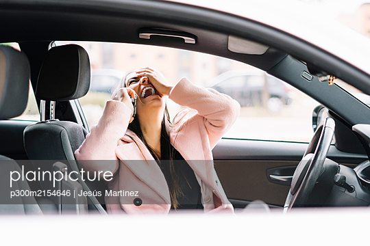 Laughing businesswoman using smartphone in the car - p300m2154646 by Jesús Martinez
