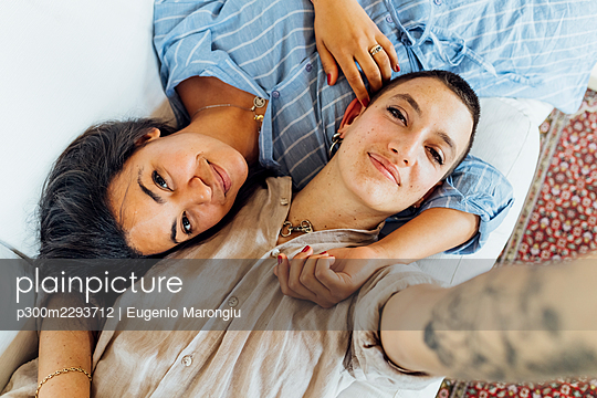 Smiling lesbian couple taking selfie while lying on sofa at home - p300m2293712 by Eugenio Marongiu