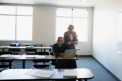 Professor and adult education student using laptop in classroom - p1192m1145733 by Hero Images