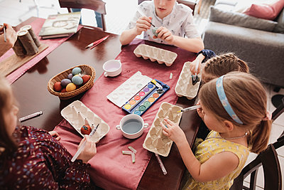 Children painting Easter eggs on table at home - p300m2103263 by Katharina Mikhrin