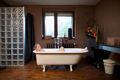 A woman taking a bubble bath in a claw foot tub - p301m714268f by Antenna photography