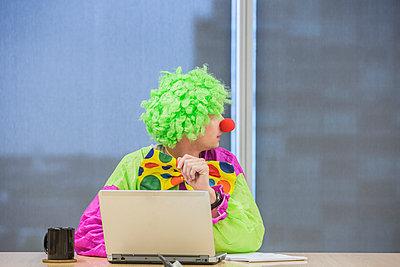 Caucasian businessman wearing clown costume in office - p555m1305932 by Hill Street Studios
