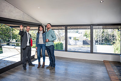 Estate agent showing couple around new home - p924m1513332 by Zero Creatives