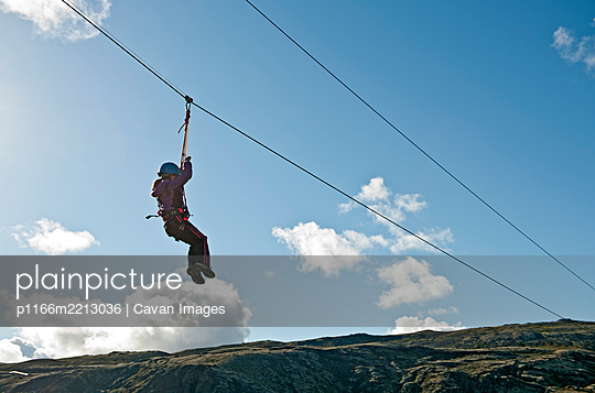 girl going down on a zip line at high rope access course in Iceland - p1166m2213036 by Cavan Images
