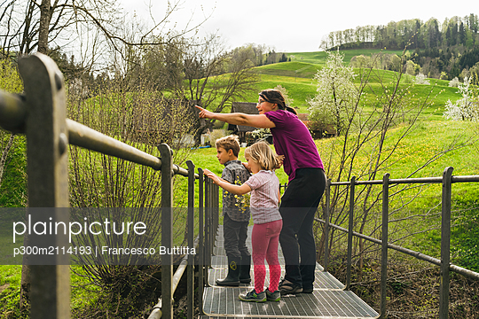 Mother with two children on a bridge in the countryside - p300m2114193 von Francesco Buttitta