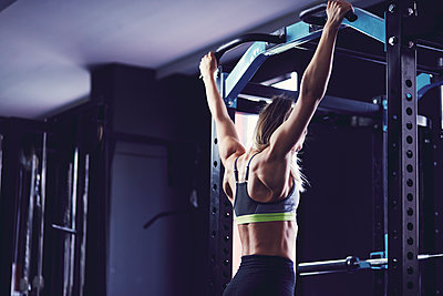 Rear profile of young woman hanging between doing chin ups at fitness centre - p1166m2095462 by Cavan Images