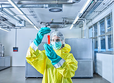 Chemist working in industrial laboratory, checking test tube - p300m2079061 by Christian Vorhofer