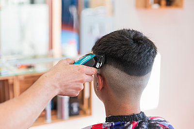 Male hairdresser using machine to do hairstyle of teenage boy at barber shop - p300m2275614 by Julio Rodriguez