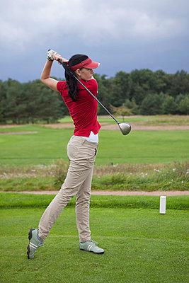A female golfer teeing off - p30119777f by Halfdark